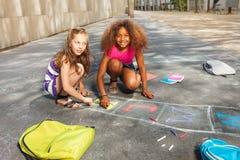 两个女孩凹道在沥青的跳房子比赛 库存照片