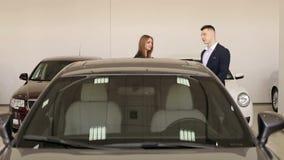 两个女孩去选择一辆新的汽车的陈列室对购买 影视素材
