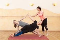 两个女孩参与瑜伽在大厅里 免版税库存照片