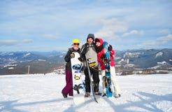 两个女孩和站立和拿着snowboads的男孩 免版税图库摄影