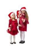 两个女孩在一件红色礼服在圣诞老人帽子站立 免版税库存图片