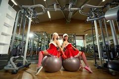 两个女孩在健身房的圣诞老人服装在圣诞节 免版税图库摄影