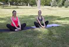 两个女孩在公园舒展他们的腿 诺维萨德 黎曼公园 免版税库存照片