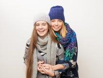 两个女孩在冬天给笑在白色背景穿衣 库存图片