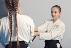 两个女孩在合气道训练的实践剑 库存照片