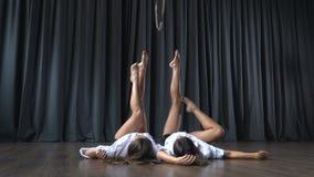 两个女孩在地板放置并且在做把戏前舒展在空中箍 影视素材