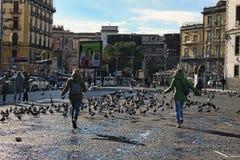 两个女孩在城市广场驾驶鸽子 三个人观看这个过程 免版税图库摄影