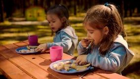 两个女孩在夏天吃在一张木桌上的早餐 库存图片