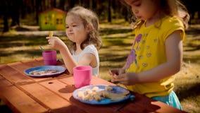 两个女孩在夏天吃在一张木桌上的早餐 免版税库存图片