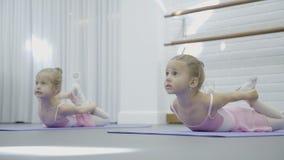 两个女孩在席子说谎并且执行舒展脊椎的发展的 影视素材