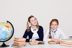 两个女孩在教室学会教训书在她的书桌地球 免版税库存图片