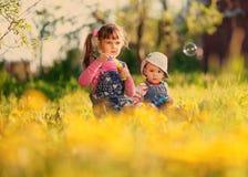 两个女孩在春天使用与肥皂泡 免版税库存图片