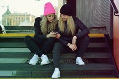两个女孩在机动性写着sms 免版税图库摄影