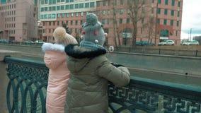 两个女孩在河堤防的少年身分在现代城市风秋天天 影视素材