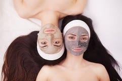 两个女孩在温泉的面部面具应用时是松弛 库存照片