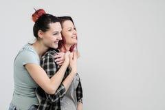 两个女孩在白色背景拥抱 同性恋女同性恋的夫妇 便衣 免版税库存图片