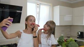 两个女孩在白色衣裳展示在智能手机穿戴了从做的红辣椒的一根髭并且做selfie照片在 股票录像