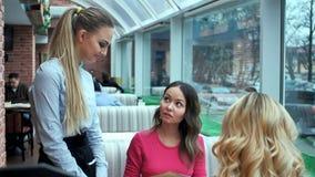 两个女孩在盘菜单选择并且与侍者协商 免版税图库摄影