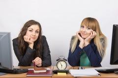 两个女孩在等待工作时间的结尾在时钟的办公室 免版税库存照片