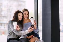 两个女孩在购物中心坐并且喝咖啡 库存照片