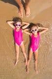 两个女孩在他的在海沙滩的海浪的后面说谎,那里是一定数量的成人人脚 免版税库存图片