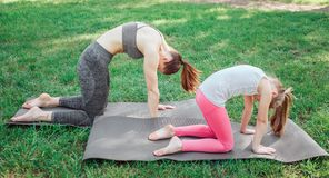 两个女孩在carimate站立并且拿着他们的后面弯曲 他们在那个姿势平衡 集中女孩 免版税库存照片