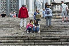 两个女孩坐台阶并且看智能手机,微笑 库存照片