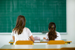 两个女孩坐在学校书桌并且看往黑板 库存图片