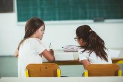 两个女孩坐在学校书桌并且看往黑板 免版税库存图片