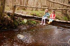 两个女孩坐在小河的桥梁渔与网 库存照片