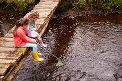 两个女孩坐在小河的桥梁渔与网 库存图片