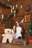 两个女孩坐在木墙壁的背景的地板在圣诞树附近 免版税库存照片
