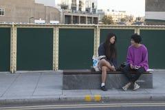 两个女孩坐在桥梁的一条长凳在百老汇路附近 免版税图库摄影