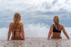 两个女孩坐海滩在从大波浪的浪花附近 免版税库存照片