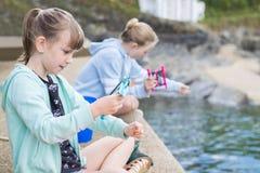两个女孩坐港口墙壁传染性的螃蟹 库存图片