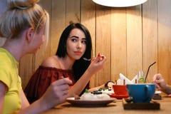 两个女孩女朋友喋喋不休,说闲话和尝试点心, 免版税库存照片