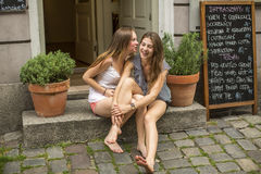 两个女孩女朋友坐咖啡馆和耳语的步 免版税库存照片