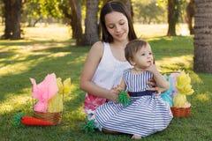 两个女孩姐妹:婴孩和青少年用复活节朱古力蛋 库存照片