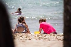 两个女孩嬉戏在度假在海滩的与沙子在一个热的夏日 库存照片