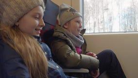 两个女孩少年坐乘客座位在现代火车的一会儿旅行 股票录像