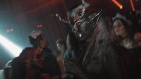 两个女孩当恶魔字符在人群跳舞在夜总会万圣夜党 影视素材