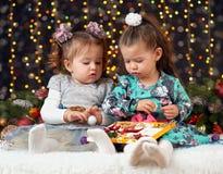 两个女孩打开在圣诞节装饰、黑暗的背景与照明和boke光,寒假概念的礼物 免版税库存照片