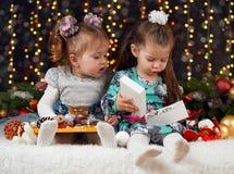 两个女孩打开在圣诞节装饰、黑暗的背景与照明和boke光,寒假概念的礼物 免版税图库摄影