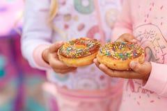 两个女孩拿着一个甜和一个大多福饼 免版税图库摄影