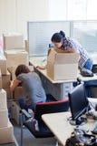 两个女孩搬入一个新的办公室 免版税库存照片
