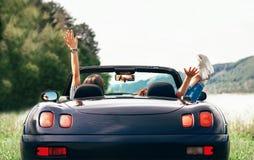 两个女孩旅客在敞蓬车汽车坐并且享用与beautifu 库存图片