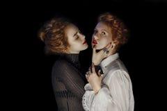 两个女孩时装模特儿画象与华美卷曲的 库存图片