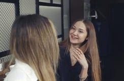 两个女孩是愉快的,并且笑有茶时间在柜台在咖啡馆 免版税图库摄影