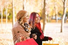 两个女孩有一次宜人的谈话在公园 免版税库存照片