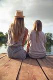 两个女孩松弛近的河 免版税图库摄影
